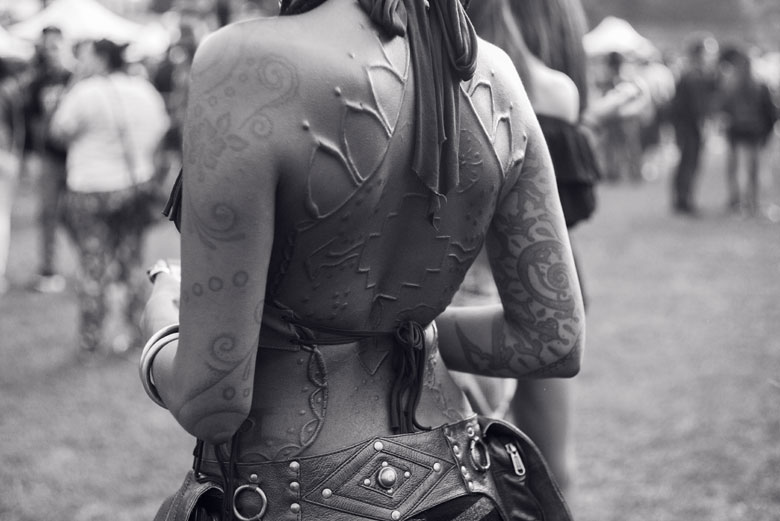 Woman's back with various tattoos.
