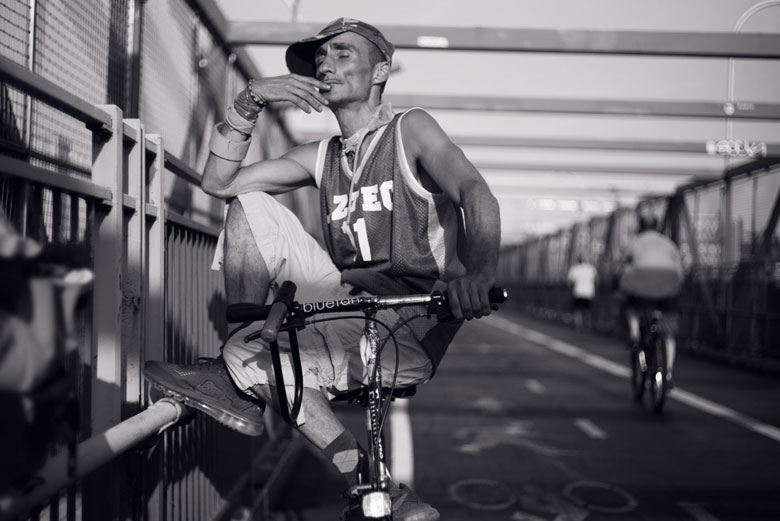 Portrait of man sitting on bike on the Williamsburg bridge.